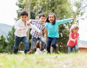 Quatre enfants courant dans le gazon